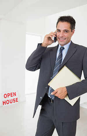 stock-photo-portrait-of-a-well-dressed-smiling-real-estate-agent-with-documents-using-mobile-phone-181083137
